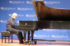 A white-haired man plays the piano onstage in front of a background spotted with Carmel Institute logos.