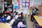 Woman in Dr. Suess hat sits in front of a room of seated children on the floor
