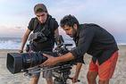 Emiliano Ruprah and crew member filming on a beach