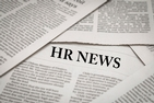 HR News as a title among a stack of newspapers