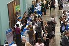 Students browse admissions fair tables in a crowded hallway