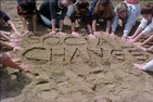 Students writing social change in the sand.