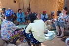women gather seated on the floor in Mali