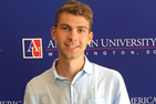 Wolf Weimer in front of American University banner