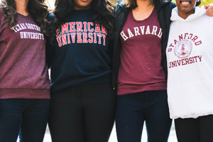Female students wearing school sweaters from left to right: Texas University, American University, and Harvard University