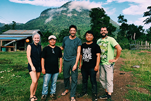 Mcgoff with production team in Laos, posing in front of a mountain