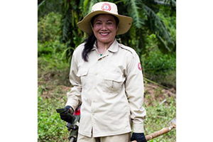 Phetsamay Sichanthavong of Lao National Unexploded Ordnance Programme (UXO Lao) standing in a field