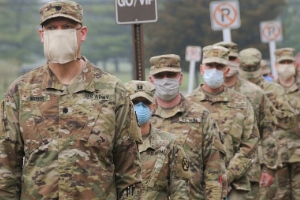 A group of US soldiers wear masks over their faces.