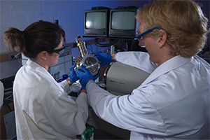 Two people in safety goggles and lab coats adjust a machine