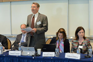 Christopher Rudolph standing and presenting at a panel discussion.
