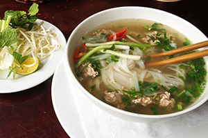Bowl of Pho, a Vietnamese dish, with chop sticks.