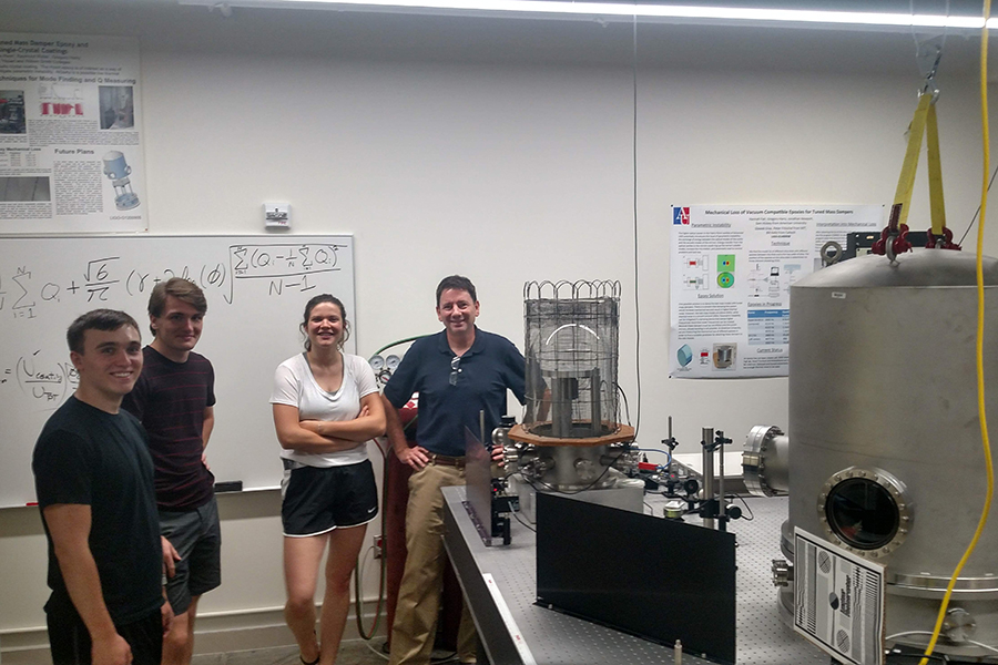 Students Maya Kinley-Hanlon, David Bialy, and Jacob Vancampen with Philip Johnson in AU's gravitational wave detector lab.