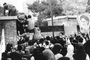 Iranian students climb up the gate at the US embassy in Tehran.