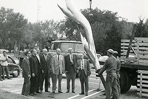 Men review the Kay Center's 14 foot bronze flame before it is placed on building