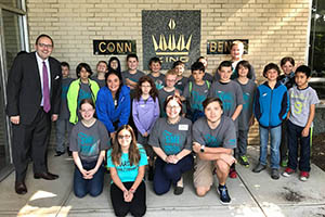 Kevin and elementary school students participating in the Alliance for Working Together (AWT) Summer Manufacturing Institute pose for a group photo after taking a tour of Conn-Selmer, a local musical instrument manufacturer.