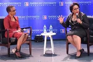 Two women sitting in chairs in front of American University backdrop.