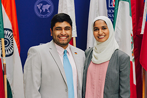 Kris Trivedi and Nuha Hamid smile in front of various national flags.