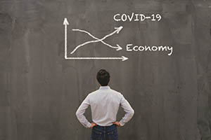 Man staring at blackboard with graph showing COVID-19 rising and economy falling