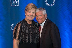 Amy and Alan Meltzer in front of blue AU background