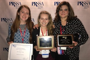 Two PRSSA members and professor Gemma Puglisi hold their award plaques