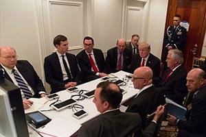 President Trump sits at a table with members of his cabinet to receive a briefing on a military strike