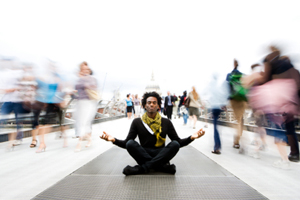 Man meditates in a crowded space