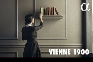 Woman placing a book on a shelf with text VIENNE 1900
